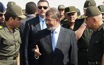 Egyptian President Mohammed Morsi, center, speaks with Minister of Defense, Lt. Gen. Abdel-Fattah el-Sissi, left, at a military base in Ismailia, Egypt, in October 2012 (photo credit: AP/Egyptian Presidency)