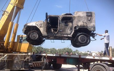 Illustrative: The charred remains of an armored vehicle are loaded onto a truck after a rocket-propelled grenade attack on a police checkpoint in el-Arish, Egypt, Friday, July 12, 2013. (photo credit: AP/Muhammed Sabry)