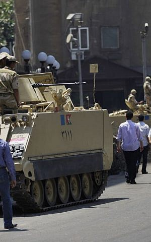 Egyptian military soldiers stand guard atop armored personnel carriers at Maspero, an Egypt's state tv and radio station, not far from Tahrir Square in Cairo Saturday, July 6, 2013. (AP Photo/Hiro Komae)