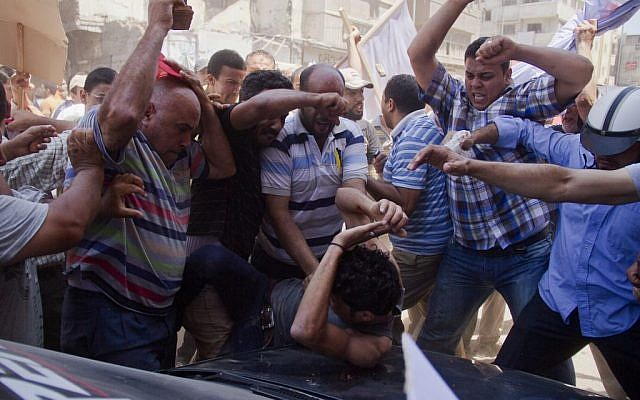 An Egyptian opposition protester is beaten by supporters of Egyptian president Mohammed Morsi, as a main raises a brick overhead, in downtown Damietta, Egypt, Wednesday, July 3, 2013. (photo credit: AP Photo/Hamada Elrasam)