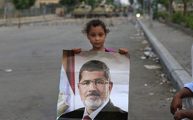 A supporter of ousted Egypt's President Mohammed Morsi poses with his photo as army soldiers guard at the Republican Guard building in Nasr City, in Cairo, Egypt, Wednesday, July 10, 2013 (photo credit: AP/Hassan Ammar)