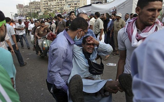 Supporters of Egypt's ousted President Mohammed Morsi carry an injured man to a field hospital following clashes with security forces at Nasr City, where pro-Morsi protesters have held a weeks-long sit-in, in Cairo, Egypt on Saturday. (photo credit: AP Photo/Khalil Hamra)