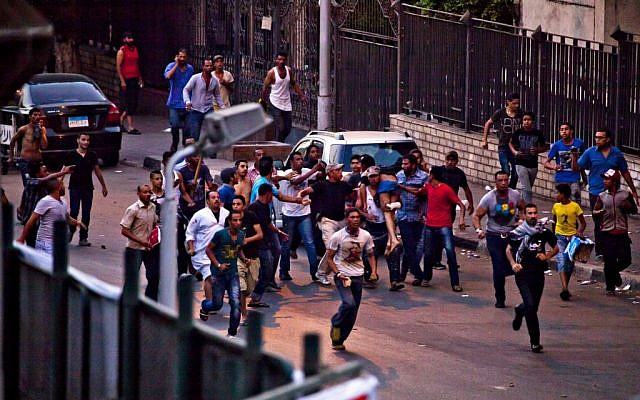 Protesters run with an injured man following clashes in the Kit Kat neighborhood of Giza, Egypt, where Tuesday, July 2 (photo credit: AP/Maya Alleruzzo)