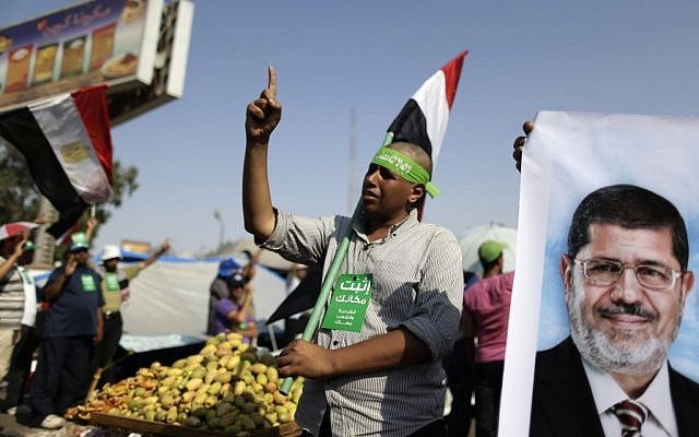 """Supporters of Egypt's Islamist president Mohammed Morsi chant slogans during a rally, in Nasser City, Cairo, Egypt, Wednesday, July 3, 2013. The green card with Arabic reads, """"stay where you are."""" (photo credit: AP Photo/Hassan Ammar)"""