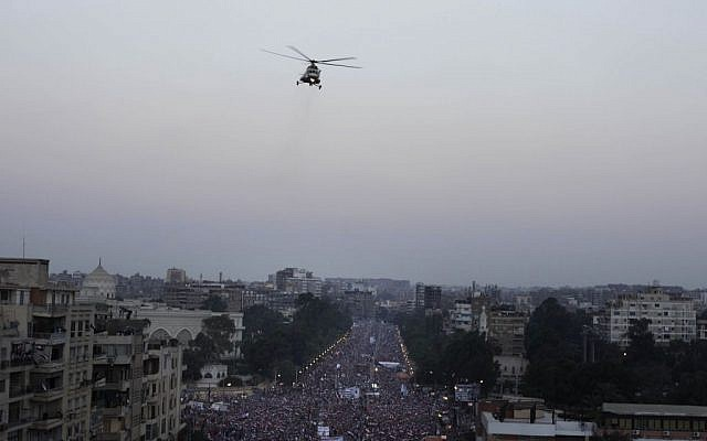A military helicopter flies over the presidential palace as opponents of Egypt's Islamist President Mohammed Morsi protest in Cairo, Egypt, on Wednesday. (photo credit: AP/Nariman El-Mofty)