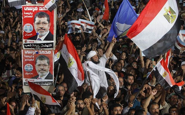 Supporters of Egypt's Islamist President Mohammed Morsi wave national flags and his posters during a rally in Nasser City, in Cairo, Egypt, on Monday, July 1, 2013. (photo credit: AP/Amr Nabil)