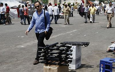 A man walks by a stand selling billy clubs used by supporters of the Muslim Brotherhood near their sit-in a suburb of Cairo, Egypt , Sunday, July 7, 2013. (photo credit: AP/Paul Schemm)