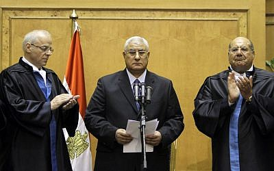 Adli Mansour, center, is applauded by by chiefs of the constitutional court after he is sworn in as the nation's interim president Thursday.(photo credit: AP/Amr Nabil)