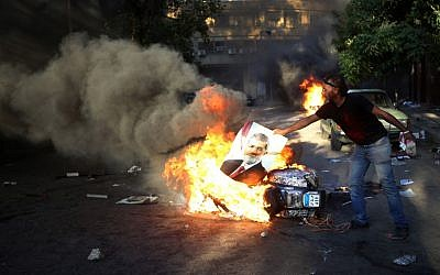An opponent of ousted President Mohammed Morsi burns a poster of the former leader during clashes against Morsi supporters, in Cairo, Egypt, Monday, July 22, 2013 (photo credit: AP/Hussein Malla)