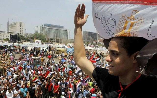 An Egyptian protester covers his head by a national flag during a demonstration against Egypt's Islamist President Mohammed Morsi in Tahrir Square in Cairo, Monday, July 1, 2013 (AP Photo/Amr Nabil)