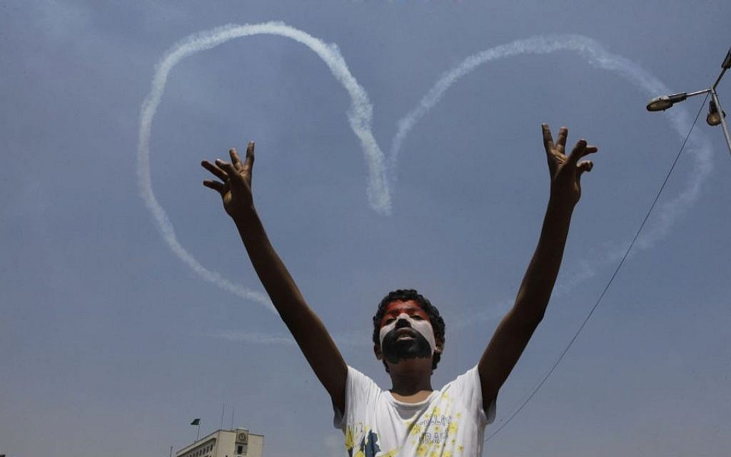 An Egyptian protester flashes V signs for a military aircraft forming a heart-shaped trail in the sky over Tahrir Square in Cairo, Egypt, Friday, July 5. (photo credit: AP/Amr Nabil)