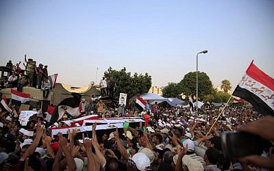 Supporters of Egypt's ousted President Mohammed Morsi carry coffins, covered with the national flag, of four men killed after Egyptian troops opened fire on mostly Islamist protesters marching on a Republican Guard headquarters Friday, in Cairo, Saturday, July 6, 2013. (photo credit: AP Photo/Khalil Hamra)