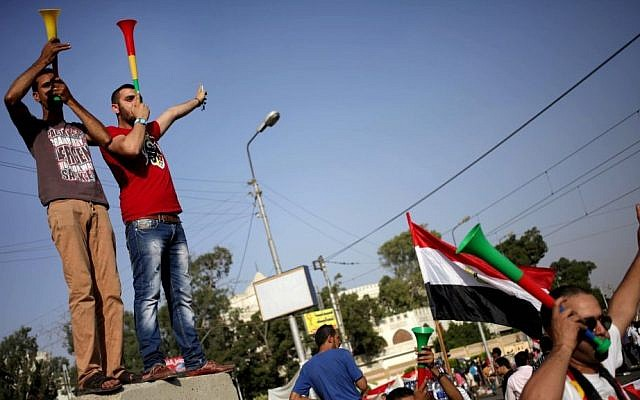 Opponents of Islamist President Mohammed Morsi celebrate after the military issued an ultimatum, outside the presidential palace, in Cairo, Egypt, Monday, July 1, 2013 (AP Photo/Khalil Hamra)