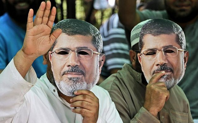 Supporters of Egypt's ousted President Mohammed Morsi wear masks with the former leader's likeness during a demonstration where protesters have installed their camp, at Nasr city, Cairo, Egypt, Friday, July 19, 2013. (Photo credit: AP/Hussein Malla)