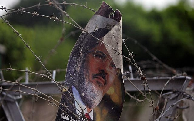 A poster of ousted president Mohammed Morsi hangs on the barbed wire at the Republican Guard building in Nasser City, Cairo, on Tuesday (photo credit: AP/Khalil Hamra)