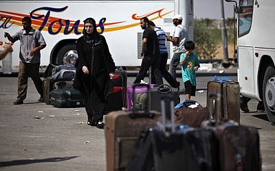 Palestinians wait with their luggage to cross into Egypt at the Rafah border crossing in the southern Gaza Strip, July 2013. (photo credit: AP/Adel Hana)