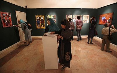 In this picture taken on Monday, July 1, 2013, Iranians visit an art gallery with paintings, in Tehran, Iran. (photo credit: AP/Vahid Salemi)