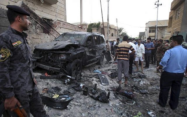 Security forces inspect the scene of a car bomb attack in Basra, Iraq, on Sunday, July 14, 2013. (photo credit: AP Photo/ Nabil al-Jurani)