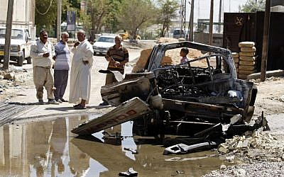 Civilians inspect the aftermath of a car bomb attack in Baghdad, Iraq, Wednesday, July 24, 2013 (photo credit: AP/Karim Kadim)