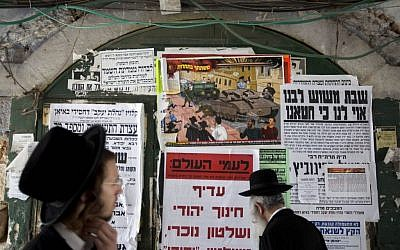 Ultra-Orthodox Jewish men walk past an anti-army draft poster in the ultra-Orthodox Mea Shearim neighborhood in Jerusalem, Sunday, July 14, 2013. (photo credit: AP/Sebastian Scheiner)