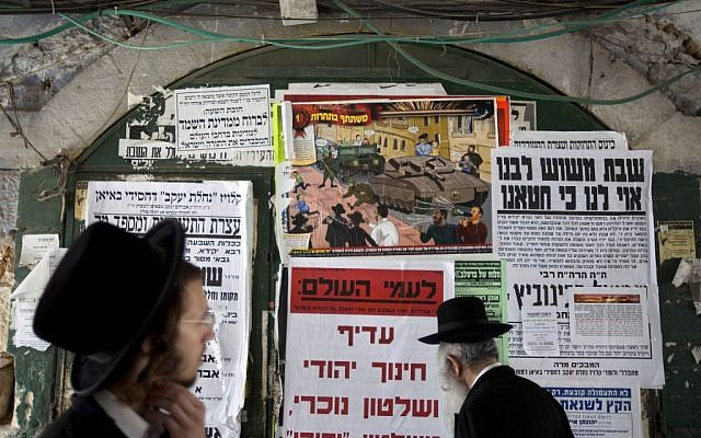 Ultra-Orthodox Jewish men walk past an anti-army draft poster in the ultra-Orthodox Mea Shearim neighborhood in Jerusalem, Sunday, July 14, 2013. (photo credit: AP/Sebastian Scheiner)
