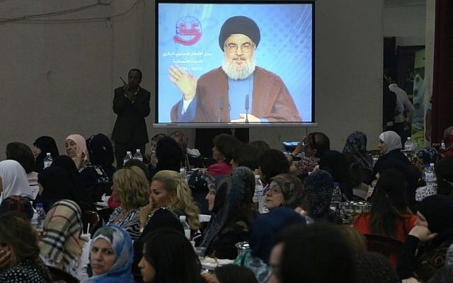 People watch Hezbollah leader Sheik Hassan Nasrallah deliver a televised speech in a southern suburb of Beirut, Lebanon on Wednesday (photo credit: AP/Hussein Malla)