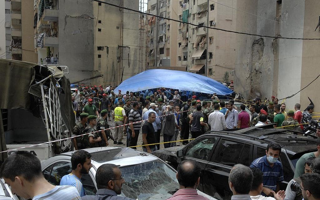 Security forces and civilians stand at the scene of a bombing in the Beir el-Abed, a southern suburb of Beirut, Lebanon, Tuesday, July 9 (photo credit: AP/Ahmed Omar)