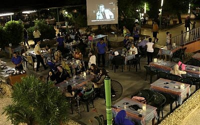 In this picture taken on Wednesday July 24, 2013, Lebanese and Syrian citizens gather at an outdoor coffee shop, as one of the Syrian popular series Al-Wiladah Men Al-Khasira (Birth from the Waist), is broadcast on a giant screen, in Beirut, Lebanon. (photo credit: AP/Hussein Malla)