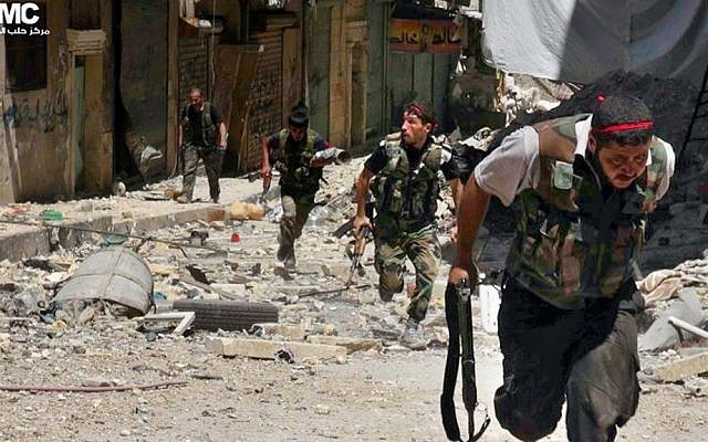 Syrian rebels run during heavy clashes with soldiers loyal to President Bashar Assad. (photo credit: AP/Aleppo Media Center AMC)