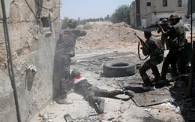 Syrian army personnel shoot toward rebel fighters during a tour for journalists organized by the Syrian Information Ministry in Damascus, Sunday, July 14, 2013. (photo credit: AP/Bassem Tellawi)