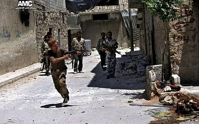 A Syrian rebel fires his weapon during heavy clashes with soldiers loyal to President Bashar Assad near Aleppo International Airport on July 2, 2013. (photo credit: AP/Aleppo Media Center AMC).