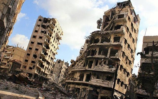 This citizen journalism image from Wednesday, July 3, shows buildings damaged by Syrian government airstrikes and shelling, in the Jouret al-Chiyah neighborhood of Homs, Syria. The photo has been authenticated by AP. (photo credit: AP Photo/Lens Young Homsi)