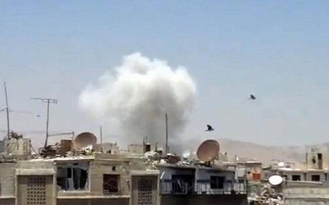 Columns of smoke billow above houses as a result of heavy bombing in Damascus, Syria, Monday July 22, 2013. (photo credit: Shaam News Network via AP video)