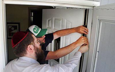 Illustrative: Rabbi Chaim Bruk, left, and Jake Matilsky affix a mezuzah to Matilsky's doorway in Helena, Montana, on June 30, 2013. (photo credit: AP/Matt Volz)