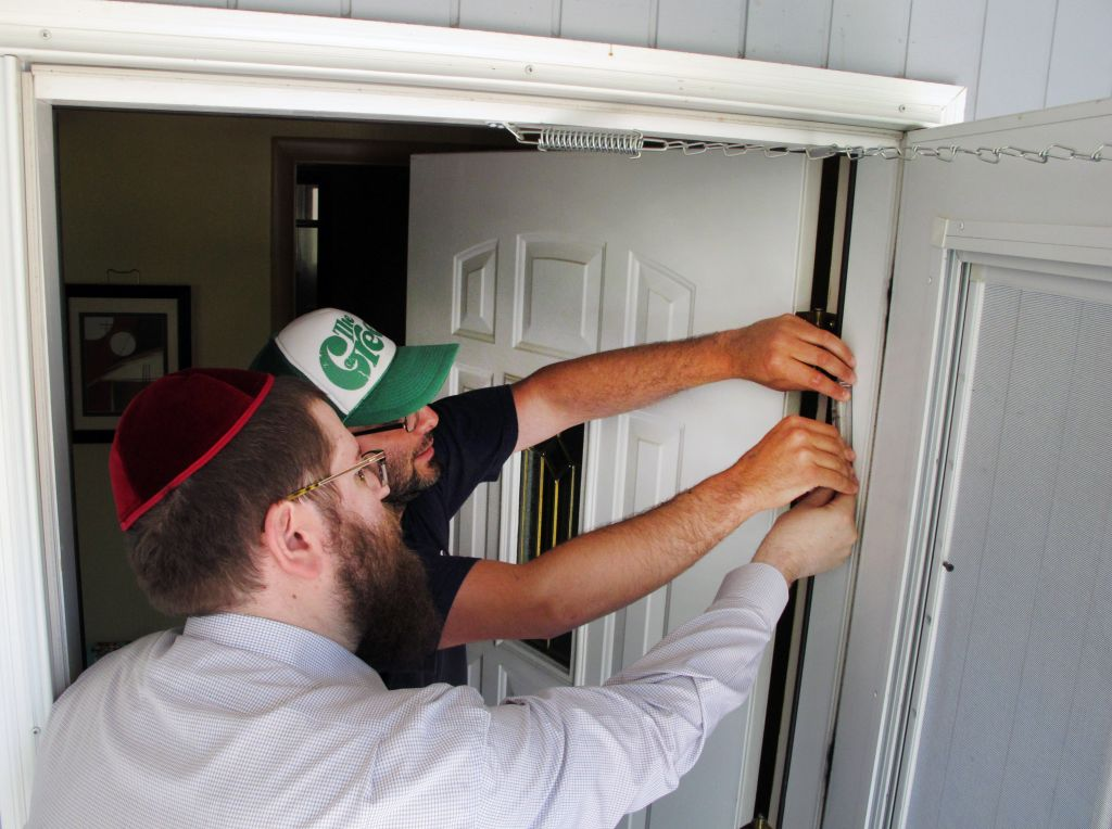 Illustrative Rabbi Chaim Bruk left and Jake Matilsky affix a mezuzah to Matilskyu0027s & Big Sky rabbi seeking stateu0027s few Jews door by door | The Times of ...