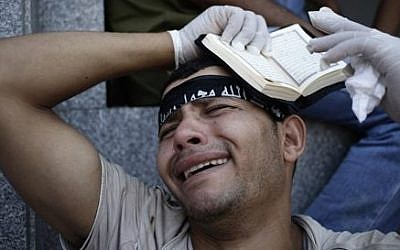 An Egyptian grieves for supporters of Egypt's ousted President Mohammed Morsi, who were killed in overnight clashes with security forces, at a field hospital in Nasr City, Cairo, July 27, 2013. (photo credit: AP Photo/Hassan Ammar)