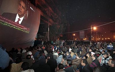 In this Wednesday, Feb. 2, 2011 file photo, anti-government protesters gathered in Cairo's Tahrir Square, watch a screen showing US President Barack Obama live on a TV broadcast from Washington, speaking about the situation in Egypt (photo credit: AP/Lefteris Pitarakis)