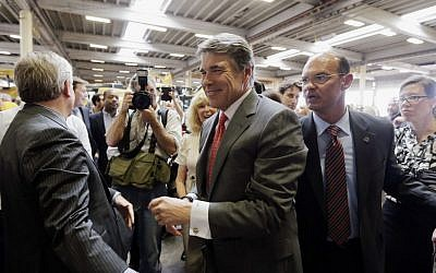 Texas Gov. Rick Perry is escorted from Holt Cat, Monday, July 8, 2013, in San Antonio after announcing he will not seek reelection (photo credit: AP/Eric Gay)