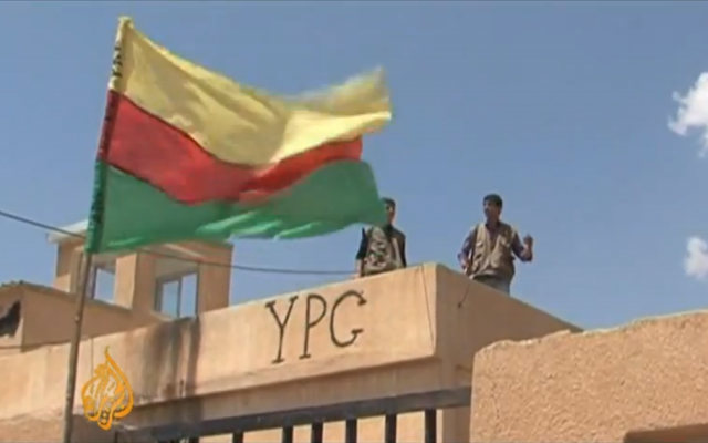 Illustrative photo of fighters from the Kurdish YPG militia alongside the group's flag in northern Syria (al-Jazeera video screenshot , YouTube)