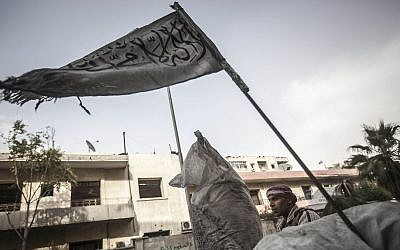A rebel fighter stands guard at a checkpoint flying an Islamic banner near the front line in Aleppo, Syria. (photo credit: AP/Narciso Contreras)