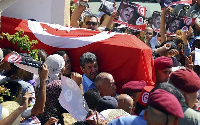 Tunisians carry the coffin of opposition politician Mohammed Brahmi out of his home in El Ghazela, in the suburb of Tunis, prior to his funeral in Tunis on Saturday. (photo credit: AP Photo/Hassene Dridi)