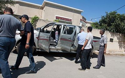 Tunisian police officers inspect Mohammed Brahmi's car in which he was shot to death outside his home in Tunis, Tunisia, on Thursday, July 25, 2013. (photo credit: AP Photo/Amine Landoulsi)