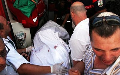 In this July 25 photo, the body of Tunisian opposition politician Mohammed Brahmi is carried into an ambulance at Mahmoud Materi hospital, north of Tunis, Tunisia. Mohammed Brahmi was shot 14 times in front of his home within sight of his family on Thursday, plunging the country into a political crisis and unleashing demonstrations around the country blaming the government for the assassination. (photo credit: AP Photo)