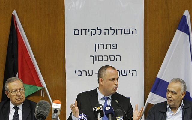 Palestinian politician and head of the Palestinian Legislative Council Abdallah Abdallah (left), Israeli parliament member Hilik Bar (center) and member of the Central Committee of Fatah Mohammad Madani seen in the Israeli parliament in Jerusalem, July 31, 2013, with the Palestinian and Israeli flags behind them (photo credit: Miriam Alster / Flash90)