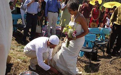 Micha'el BedarShah washes the feet of his bride, Aumatma, during the first wedding ceremony held at Urban Adamah, a Jewish educational farm in Berkeley, Calif., June 30, 2013. (photo credit: courtesy Micha'el BedarShah/JTA)