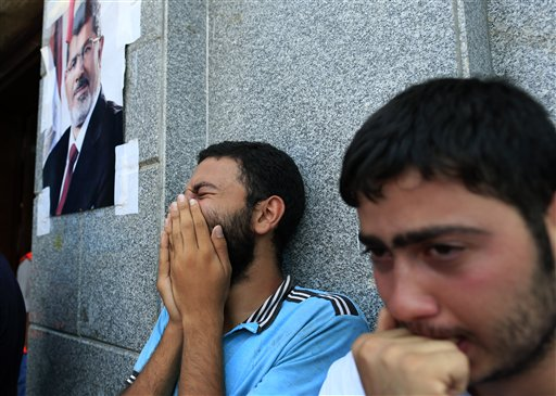 Egyptians mourn supporters of Egypt's ousted President Mohammed Morsi who were killed in overnight clashes with security forces, in a field hospital, in Nasr City, Cairo, Egypt, Saturday, July 27, 2013 (photo credit: AP Photo/Hassan Ammar)