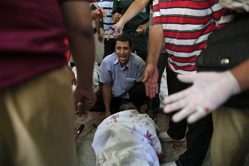 An Egyptian man sits beside his comrade, a supporter of Egypt's ousted President Mohammed Morsi, injured during clashes with security forces at Nasr City, where pro-Morsi protesters have held a weeks-long sit-in, in a field hospital in Cairo, Egypt, Saturday, July 27, 2013 (photo credit: AP Photo/Hassan Ammar)