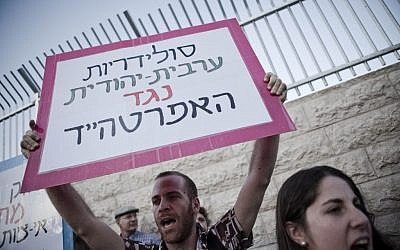 An Israeli man holds up a placard that reads, 'Arab-Jewish solidarity against apartheid,' outside a dedication ceremony for the Jewish neighborhood of Maale HaZeitim, inside the Arab-dominated Ras el Amud in East Jerusalem (photo credit: Ruben Salvadori/Flash90)