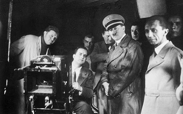 Adolf Hitler, Nazi minister of propaganda Joseph Goebbels (right) and others watch filming at Universum Film AG, the principal film studio in Germany at the time, in 1935. (Photo credit: CC-BY-SA, Bundesarchiv, Bild 183-1990-1002-500, Wikipedia)