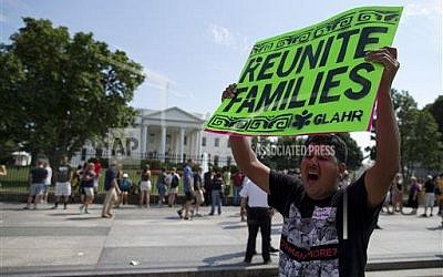 A protester holds a sign advocating for the immigration bill during a rally in front of the White House in in Washington, Wednesday, July 24, 2013 (photo credit: AP Photo/Evan Vucci)